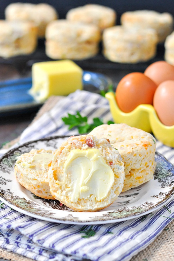 A close up of cheddar biscuits cut in half and spread with butter sitting on a plate