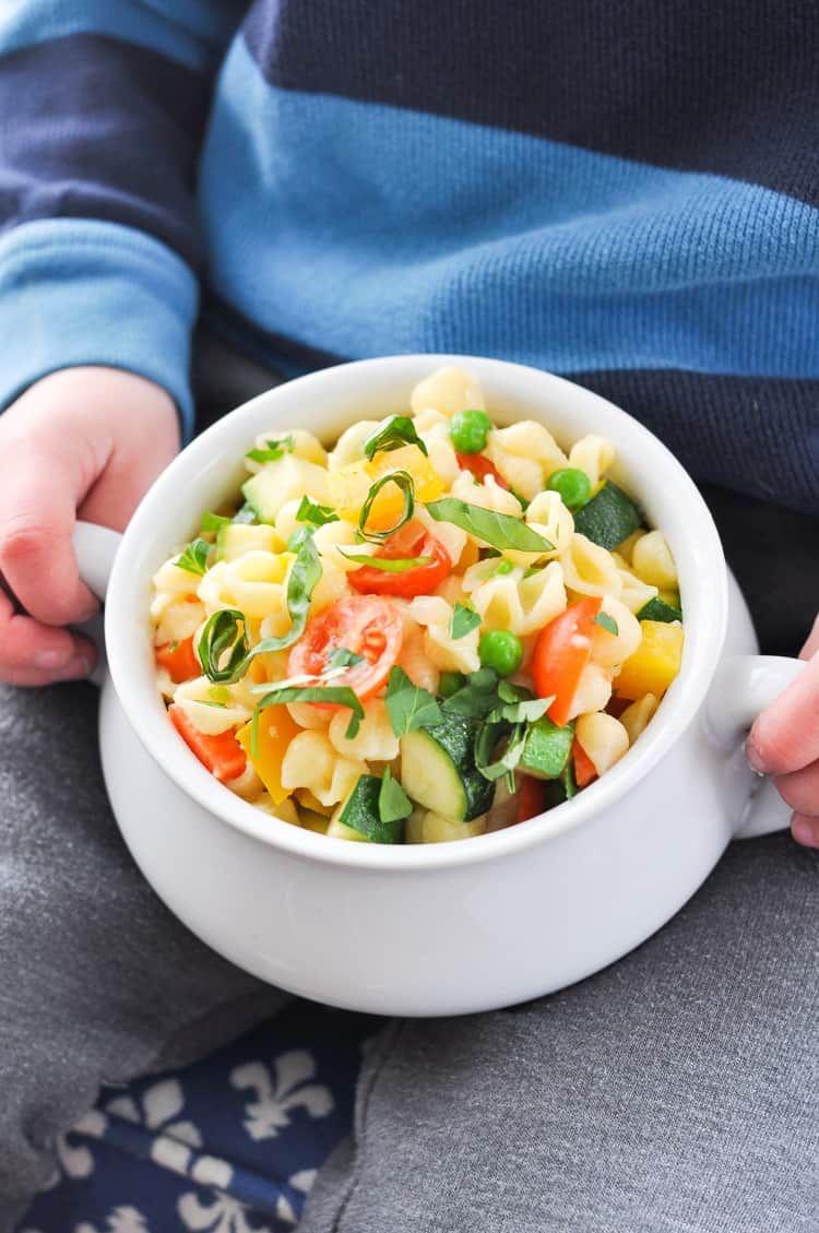 A small boy holding a bowl of Creamy Pasta Primavera