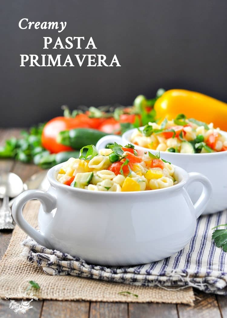 A white bowl filled with creamy pasta primavera sitting on a wooden table