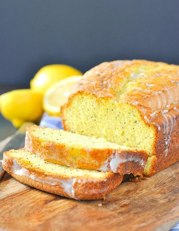 Loaf of lemon poppy seed bread sliced on a cutting board