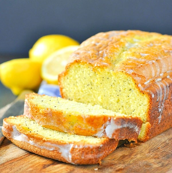 Square photo of a loaf of lemon poppy seed bread on a cutting board with slices cut