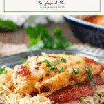 Front shot of baked healthy chicken parmesan on a plate of pasta with text title box