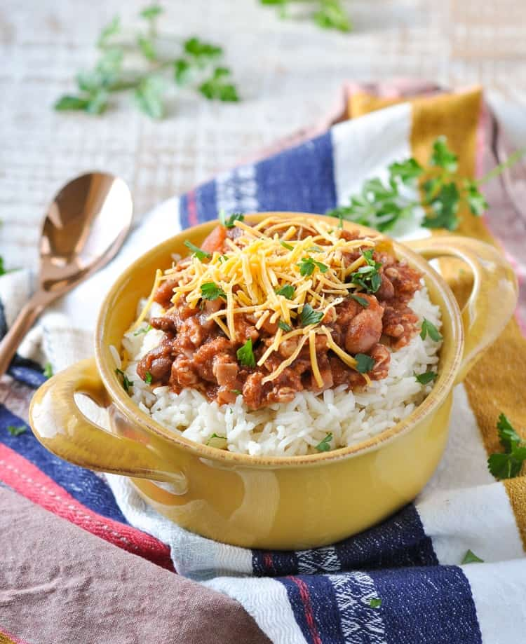 Rice and beans in a bowl topped with herbs and cheese