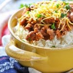 Rice and beans in a yellow bowl topped with cheese