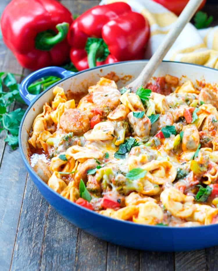 One Skillet Chicken Sausage and Tortellini in a blue skillet with a wooden spoon