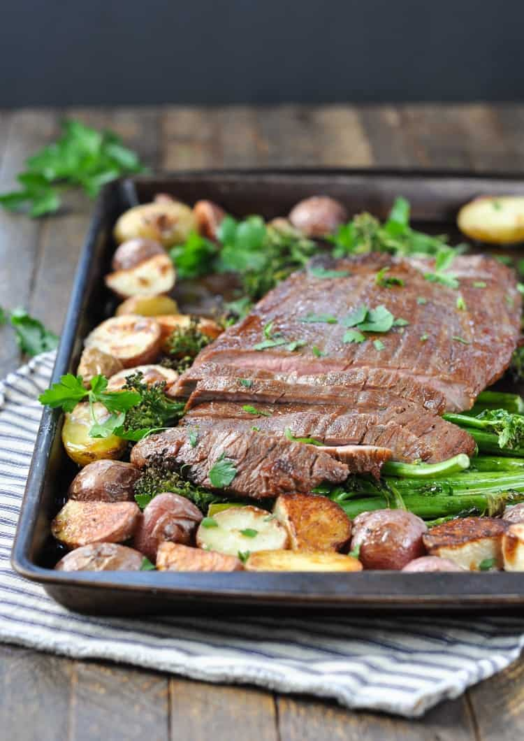 Sheet Pan Flank Steak on with Crispy Potatoes and Broccolini sitting on a wooden surface