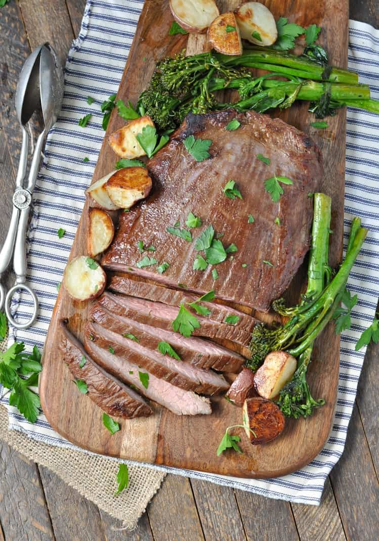 An overhead shot of Flank Steak with Crispy Potatoes and Broccolini on a wooden board