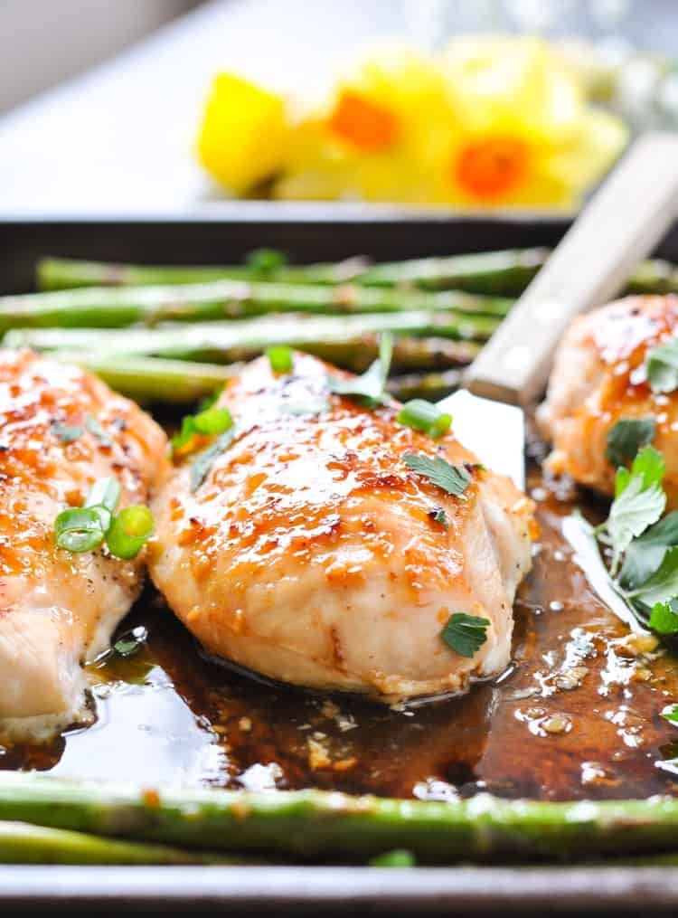 A close up of honey apricot chicken on a tray with asparagus