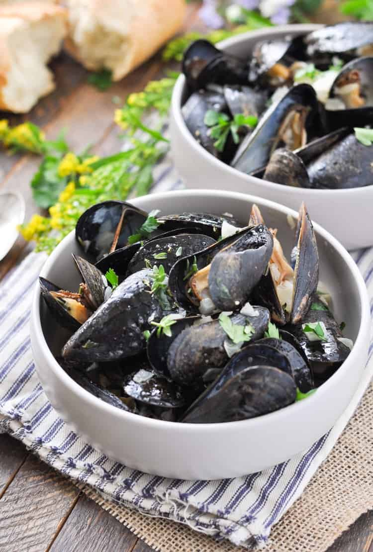 A white bowl of steamed mussels topped with green herbs