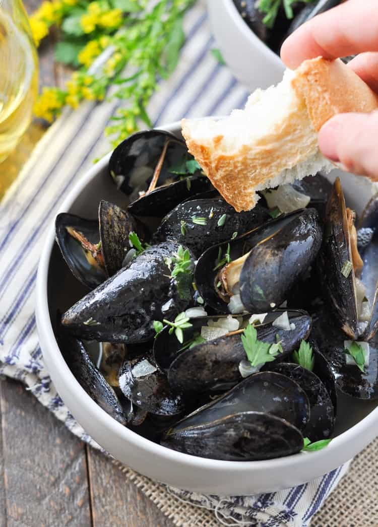 A close up Steamed Mussels  in a bowl with a slice of crusty bread