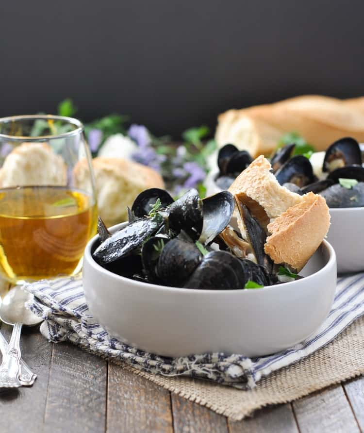 A side shot of Steamed Mussels in a bowl with crusty bread