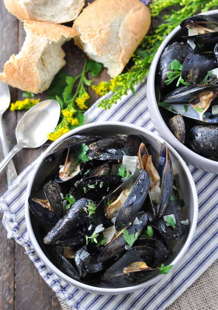 An overhead shot of Steamed Mussels in Garlic and Herb Wine Sauce in two bowls