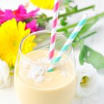Overhead shot of a tropical coconut smoothie in a glass surrounded by flowers