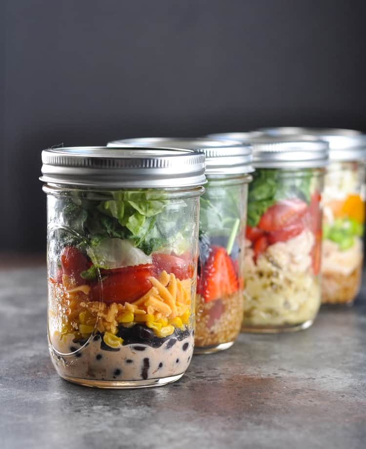 Jars of mason jar salads lined up on a table