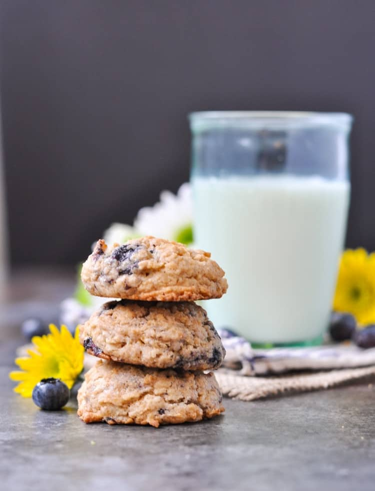 A stack of blueberry easy oatmeal cookies with a glass of milk in the background