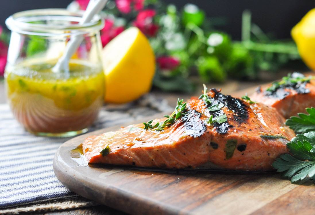 Garlic and Herb Salmon Marinade on a salmon fillet sitting on a wooden board