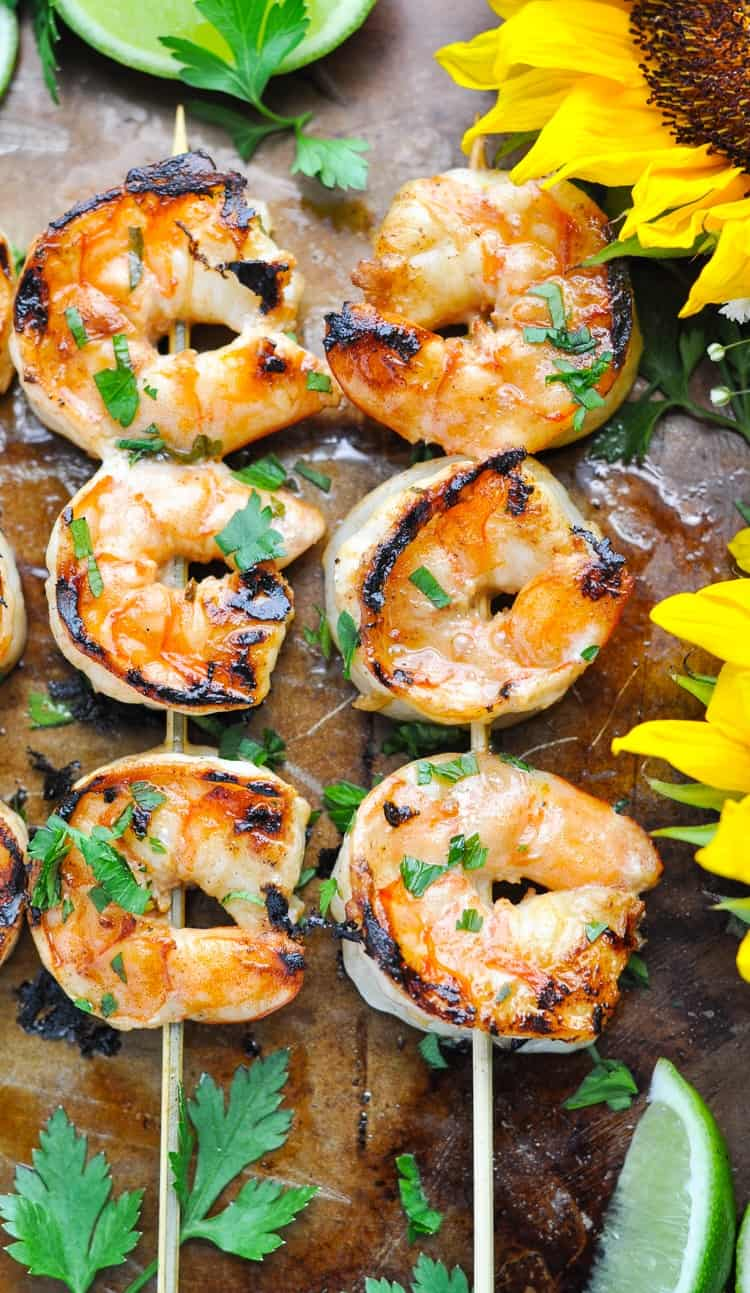 An overhead shot of two skewers of marinated grilled shrimp on a baking tray