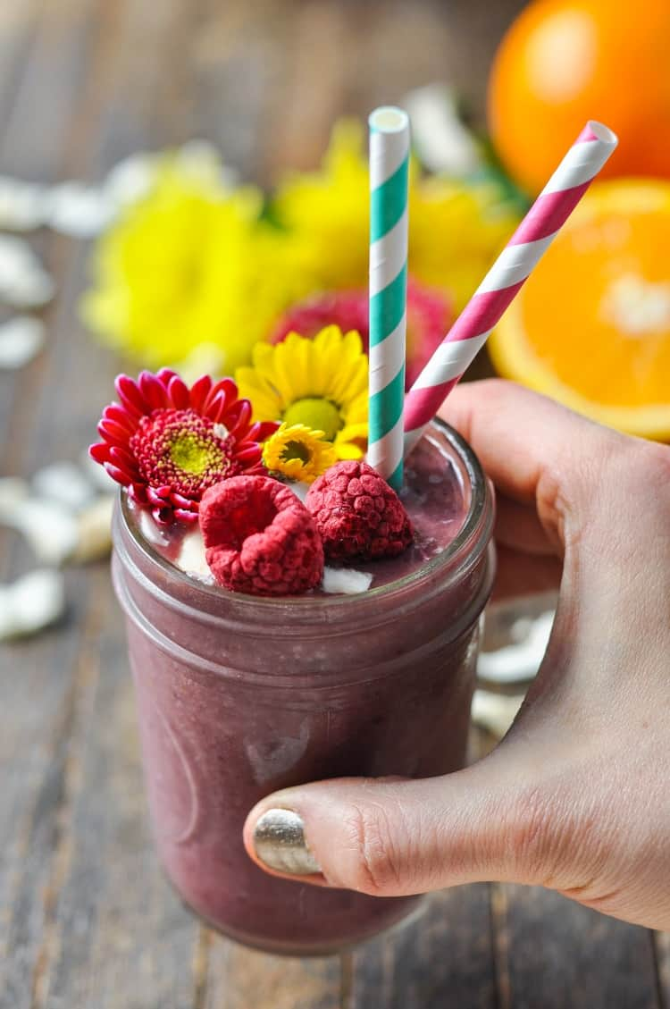 A close up of a southern ambrosia smoothie in a mason jar with two colored straws and flowers on top