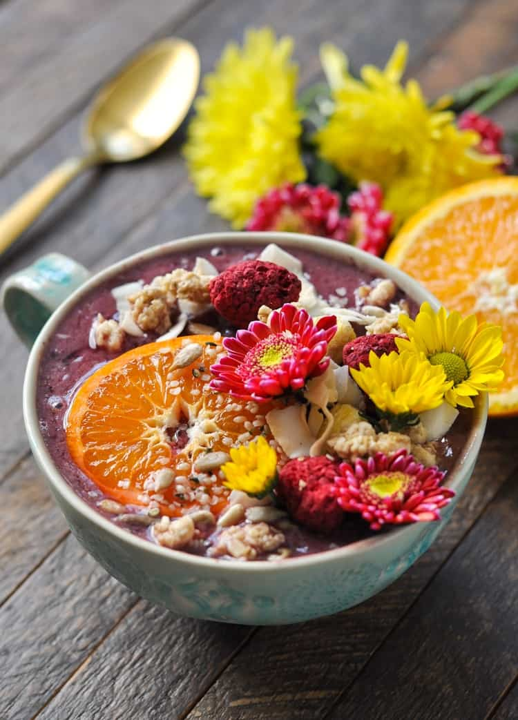 A close up of a southern ambrosia smoothie in a large mug topped with flowers , granola and a slice of orange