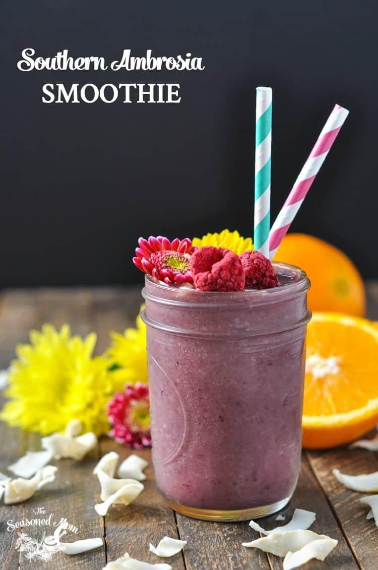 A mason jar filled with a southern ambrosia smoothie with cut orange in the background
