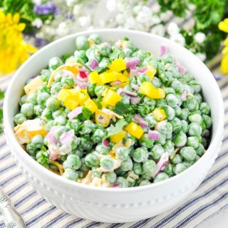 Southern pea salad in a white bowl surrounded by fresh flowers