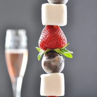 A close up of a strawberry chocolate donut kabob with a glass of wine in the background
