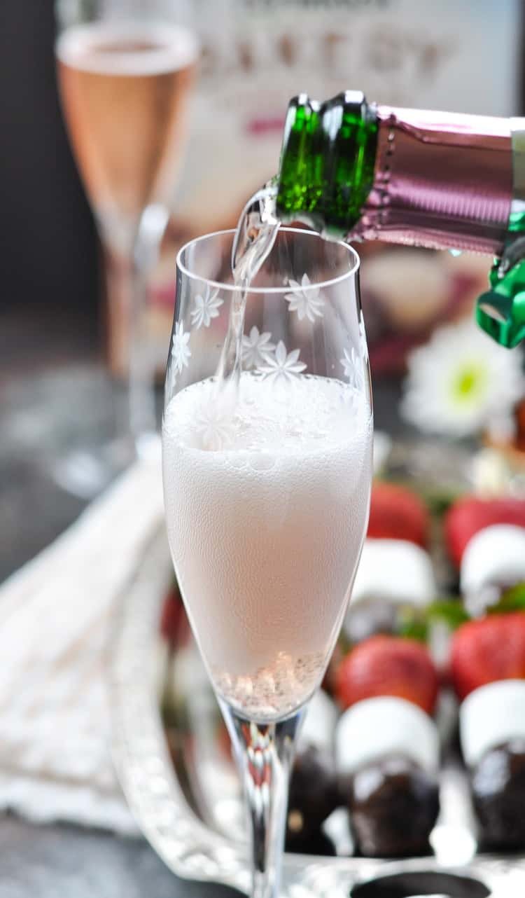 A close up of a glass of champagne getting poured in a glass with strawberry chocolate donut kabobs in the background