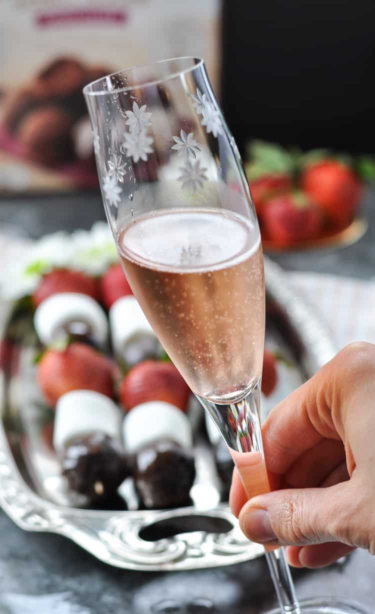 A close up of glass of pink champagne with strawberry chocolate donut kabobs in the background