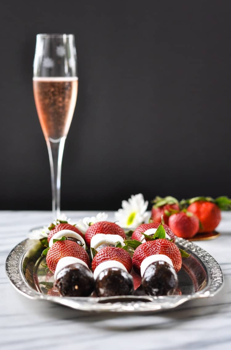 A side shot of strawberry chocolate donut kabobs on a silver plate with a glass of pink sparkling wine in the background