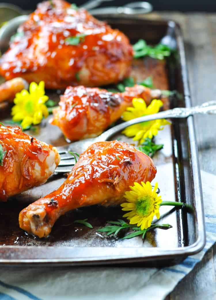 Apricot glazed chicken on a baking sheet with a fork