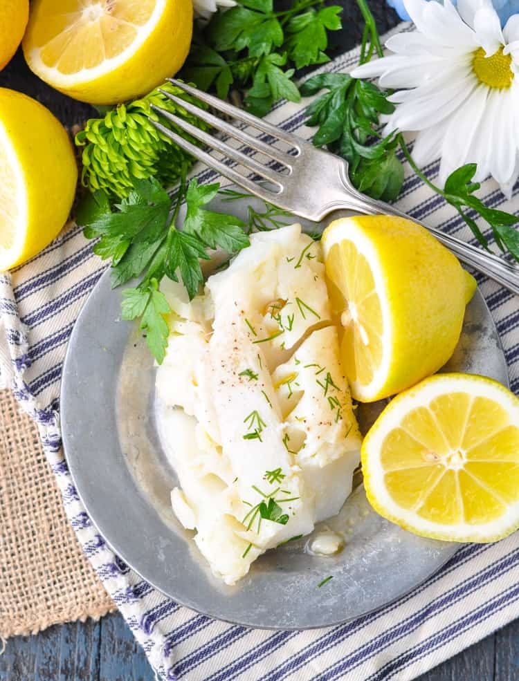 An overhead shot of Lemon Garlic Cod on a plate with a fork and lemon slices