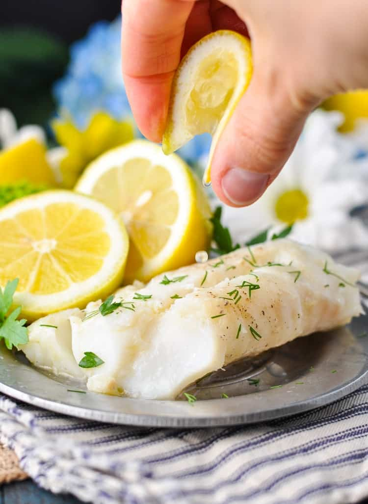 Squeezing lemon juice over a fillet of cod