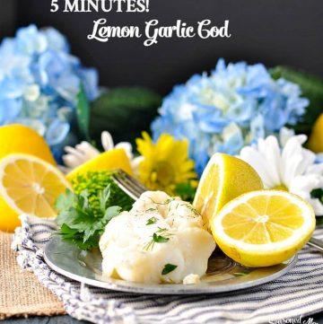 Lemon garlic cod on a plate with slices of lemon