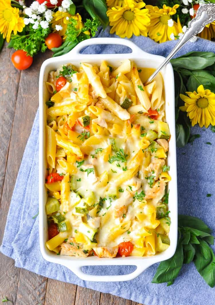 An overhead shot of a white casserole dish filled with pasta with zucchini, tomatoes and chicken
