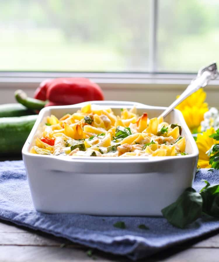 A side shot of summer pasta with zucchini in a casserole dish with a serving spoon