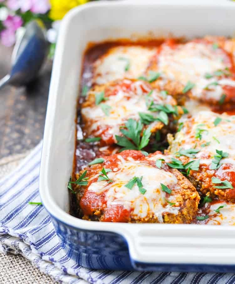 Close up of eggplant parmesan in blue baking dish