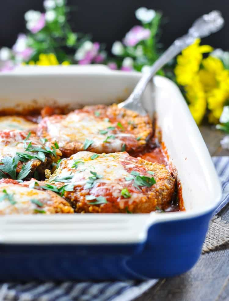 Blue baking dish with eggplant parmesan and silver serving spoon