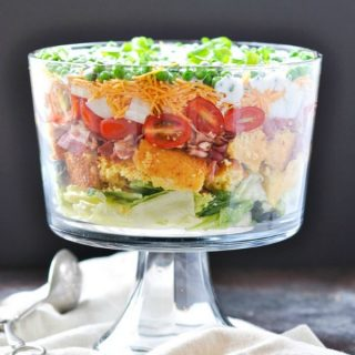 Layered Southern Cornbread Salad with bacon and cheese in a large glass serving bowl