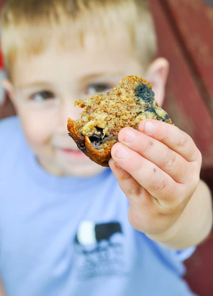 A photo of a boy holding whole wheat banana muffins with blueberries
