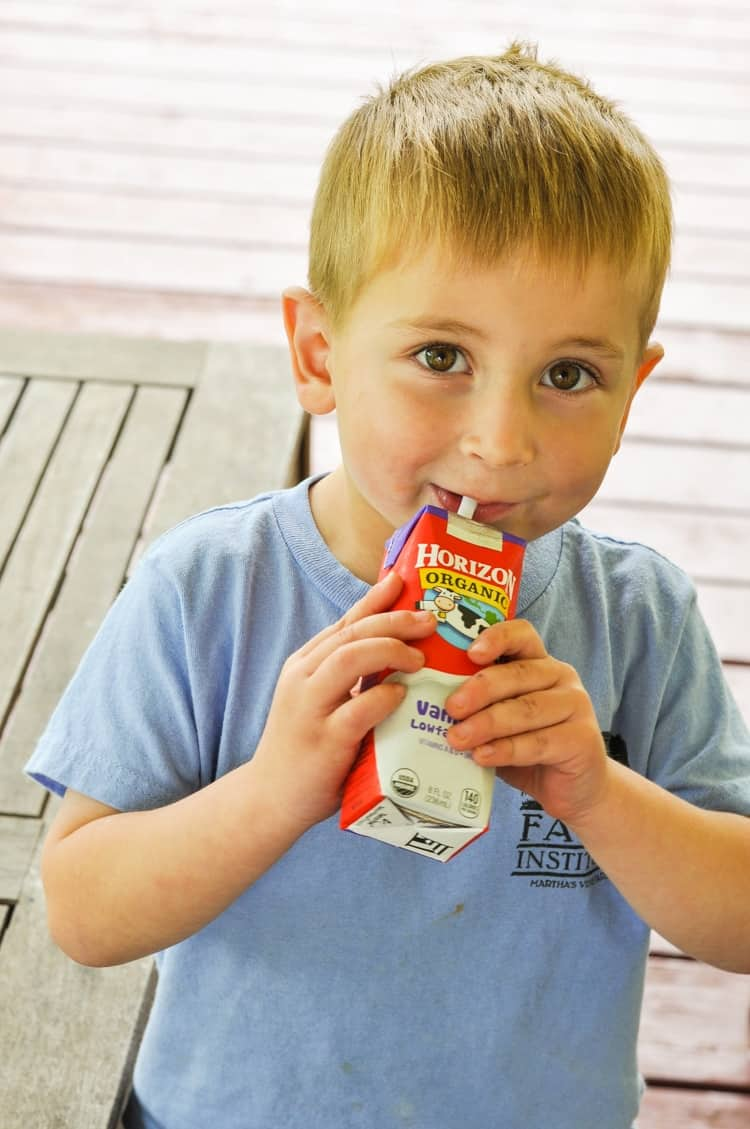 A photo of a young boy holding a carton of milk