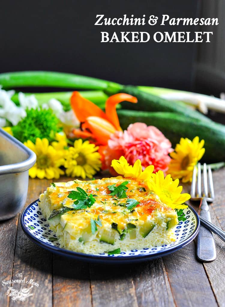 A photo of a baked zucchini and parmesan omelet on a plate with flowers in the background, easy zucchini recipes
