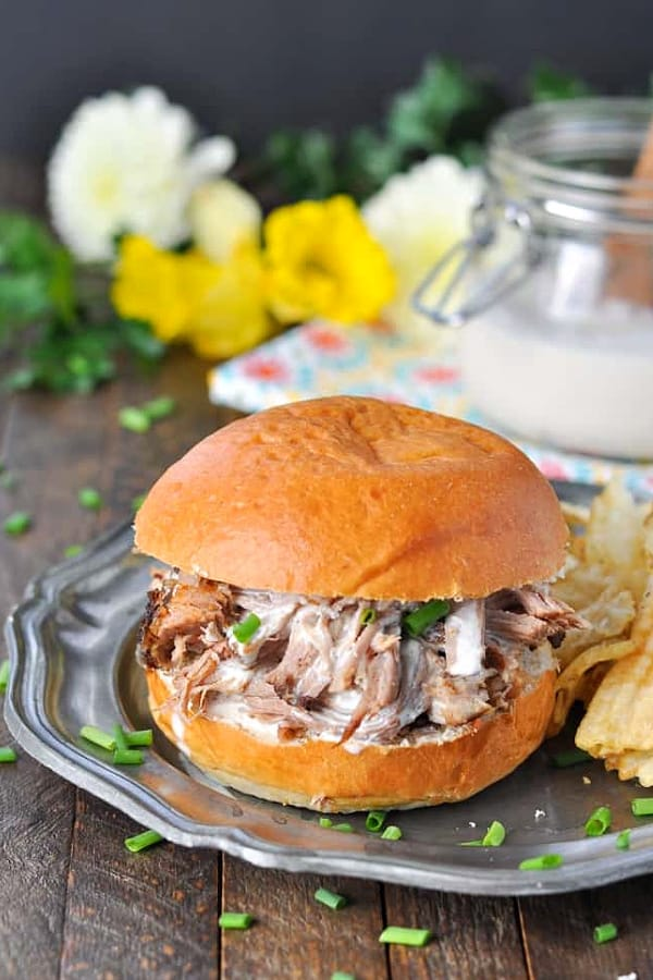 Slow cooker pulled pork with alabama white bbq sauce on a sandwich bun