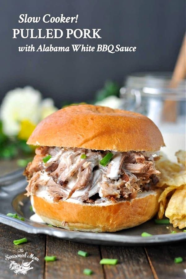 Front shot of a slow cooker pulled pork sandwich with white bbq sauce and text title overlay