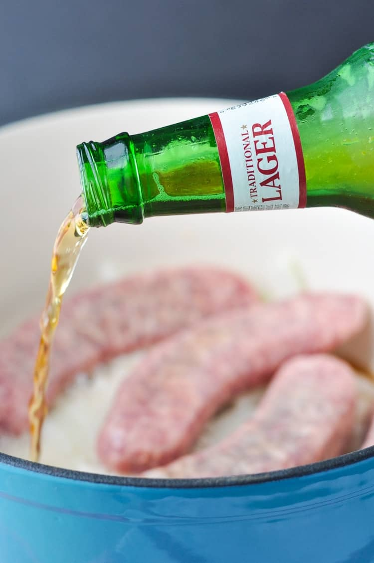 A process shot of pouring beer on top of sausages in a pot to make beer brats