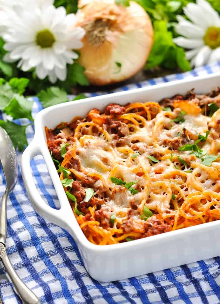 A close up of Easy Baked Spaghetti in a white dish topped with herbs