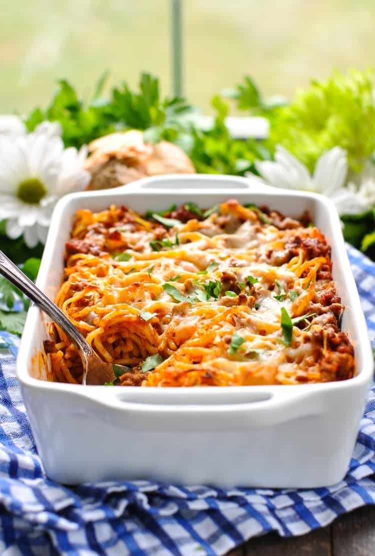 Easy baked spaghetti in a white baking dish with a serving spoon and flowers in the background