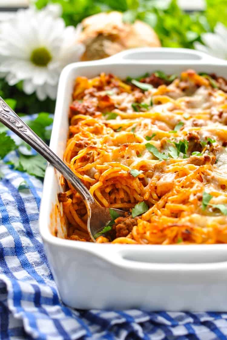 Easy baked spaghetti in a white baking dish with a serving spoon and chopped parsley