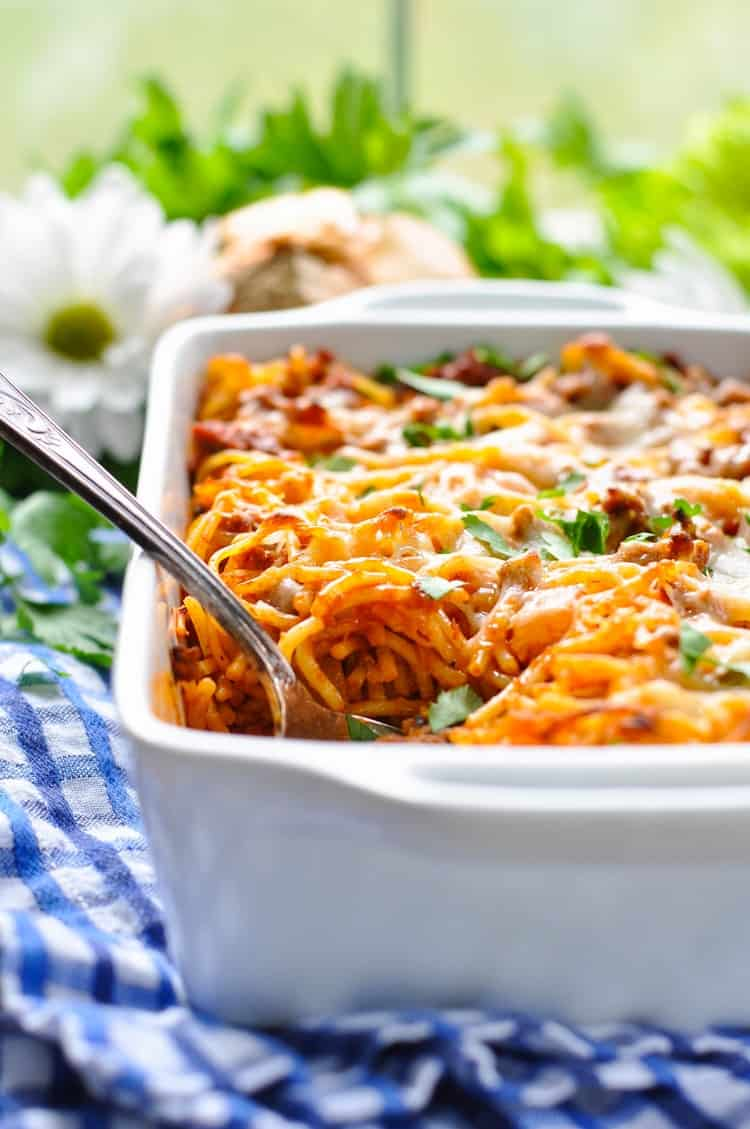 A side shot of Easy Baked Spaghetti in a casserole dish with a large serving spoon