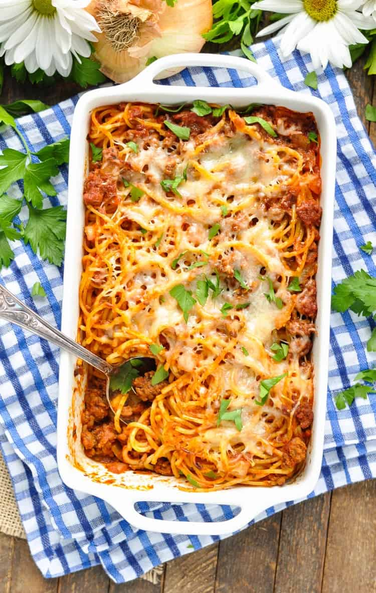 An overhead shot of easy baked spaghetti casserole topped with chopped herbs