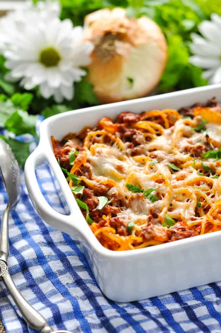Easy Baked Spaghetti in a white casserole dish sitting on a blue checked tablecloth